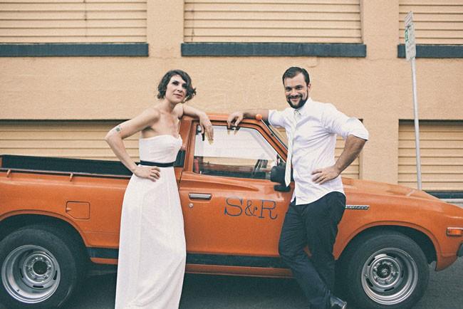 Bride and groom standing in front of orange truck