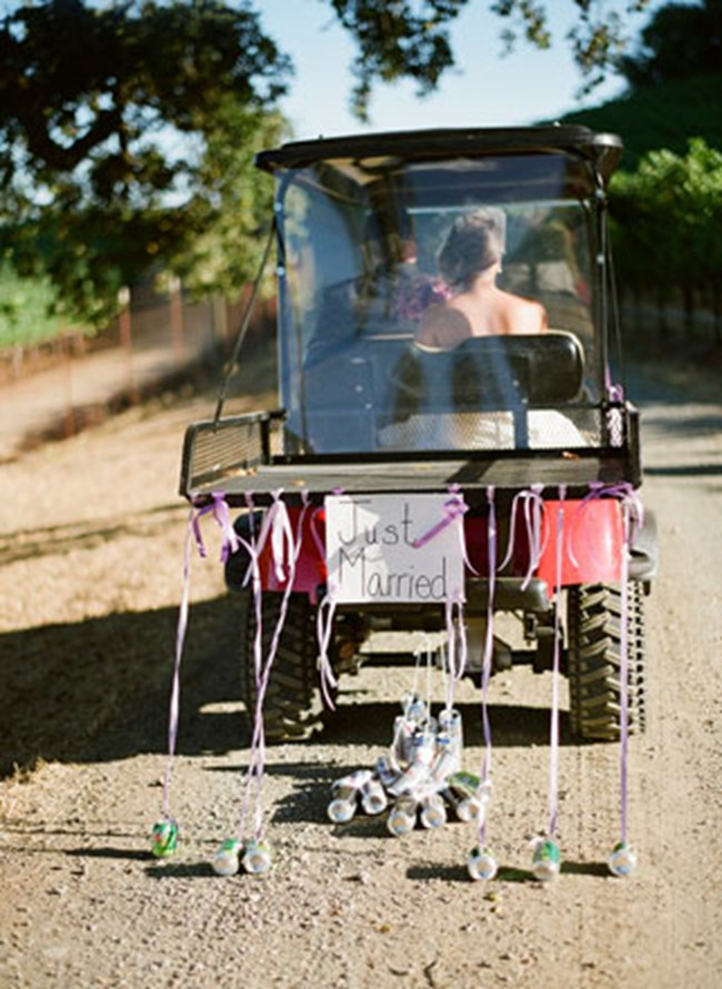 Bride and groom riding a golf cart with a just married sign