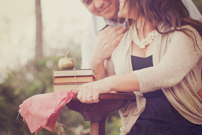Couple sitting at a vintage school desk with books and golden apple