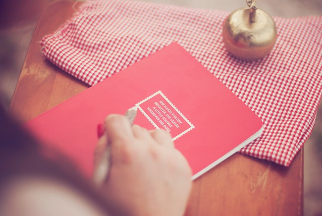Red note book with a golden apple
