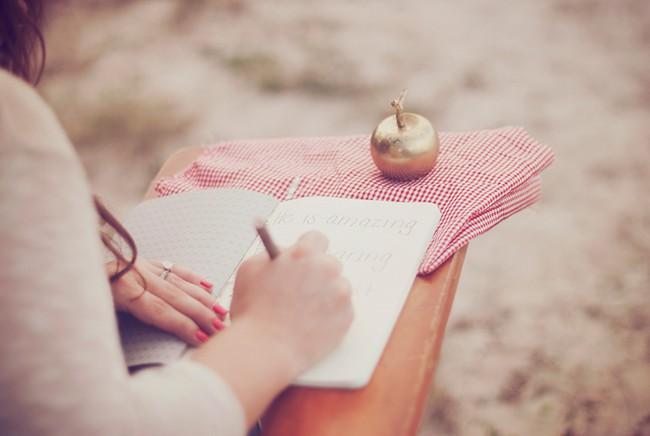 Women writing something down sitting at a vintage school desk. Golden apple