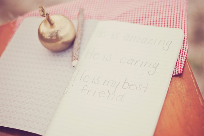 Note book with writing and a golden apple with a pencil