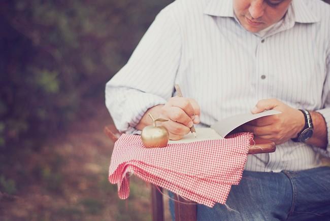 Man writing something down at a vintage school desk. Golden apple.