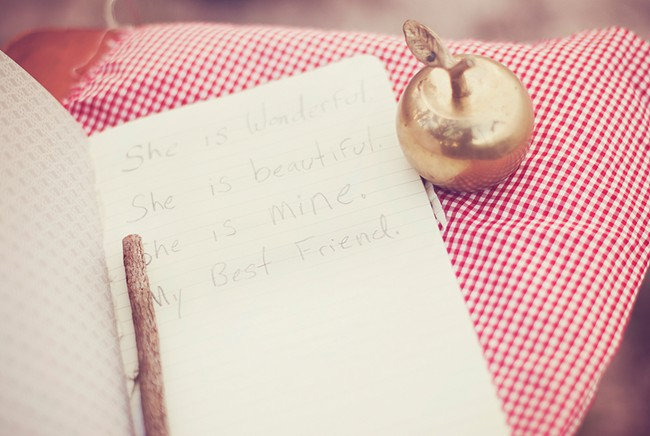 Note book with writing a pencil and a golden apple