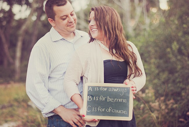 A couple holding a chalk board