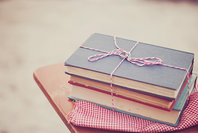 Engagement ring places on vintage books on top of a vintage school desk