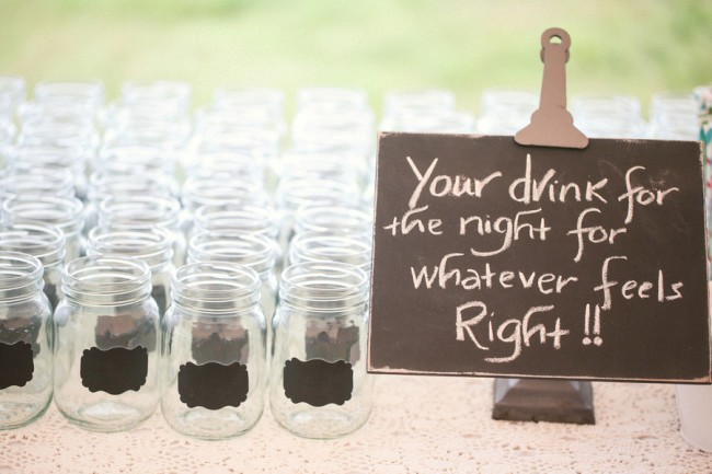 Mason jars lined up on table for guest at wedding with chalkboard label for names