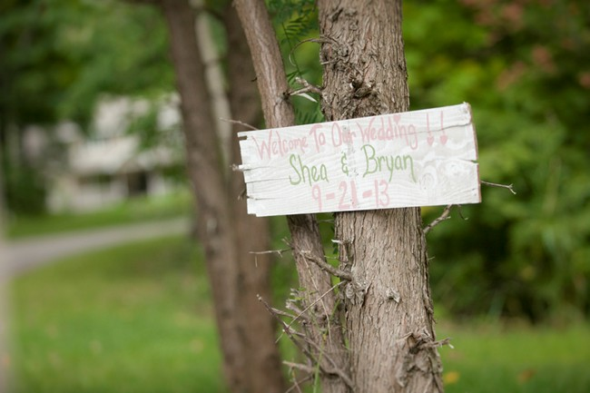 "Wooden ""welcome to our wedding"" sign hung on a tree"
