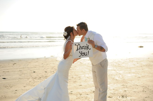 bride and groom kissing holding a thank you sign on the beach