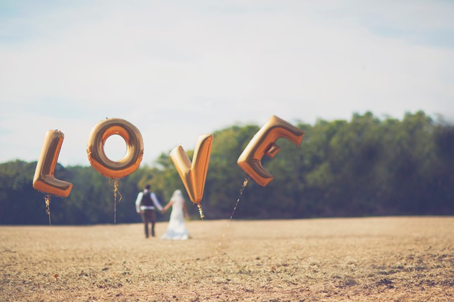 bride and groom with gold letter balloons that spell L-O-V-E