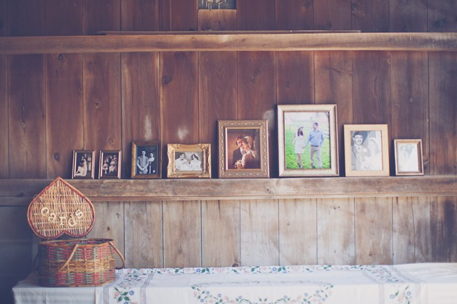 card table at wedding recepetion with framed photos of family on wood plank wall