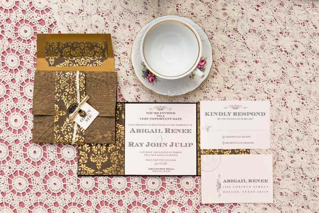 Overhead photo of Alice in Wonderland styled shoot invite & RSVP card on white doily cover with teacup