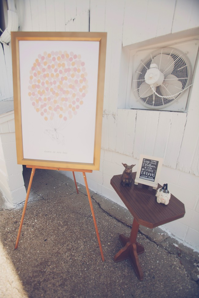 easel with picture of balloons for guests to sign as guestbook