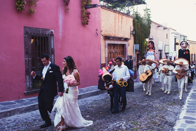Bride and groom walking up street with a mariachi band