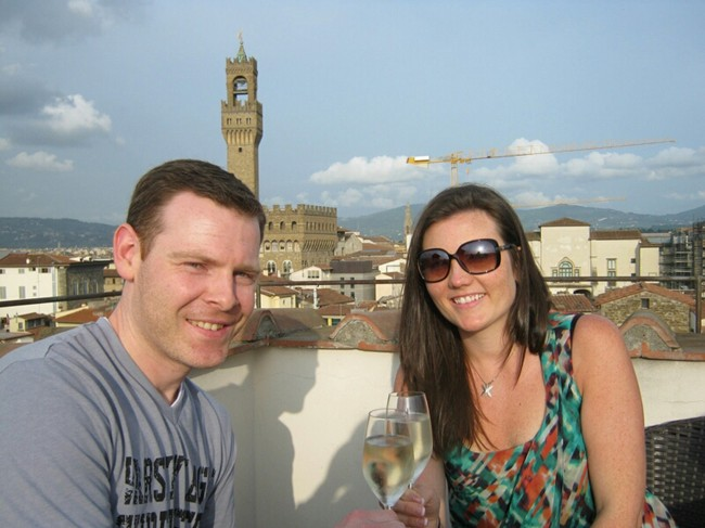 Couple sitting on top of Torre guelfa in florence italy