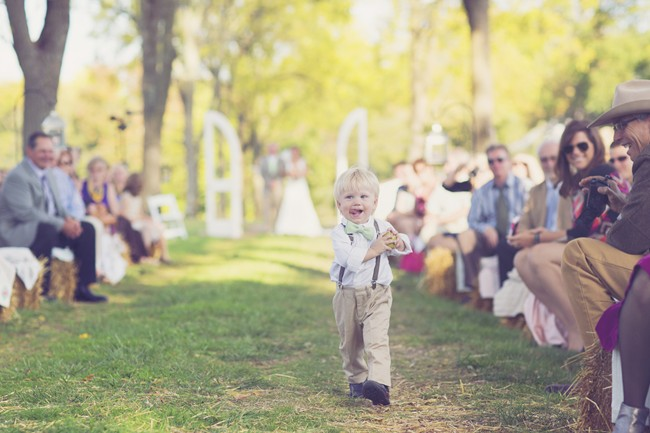 ring bearer walking down aisle as guests sit on haystacks