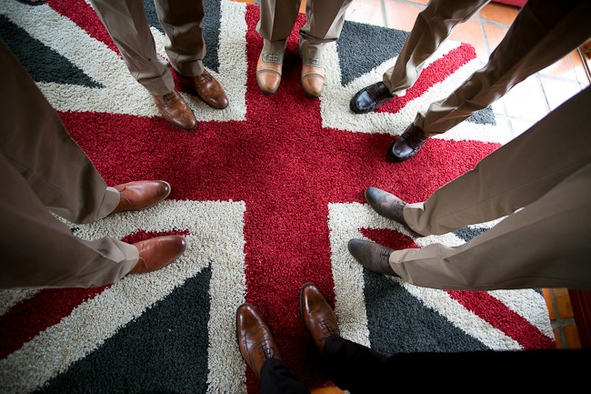 6 guys standing on a carpet with a British flag pattern