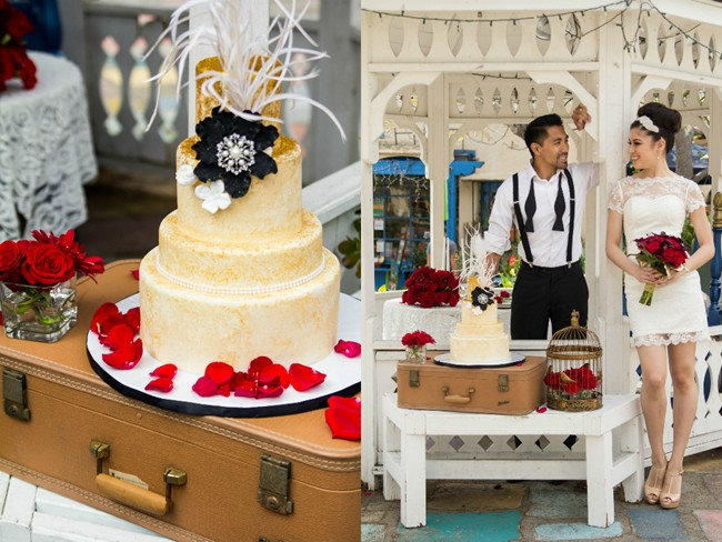 Bride and groom in balboa park under gazebo holding red roses and a gold cake wearing  Iselle Design Studio