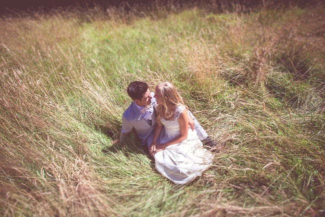 Bride and groom laying in a field captured by aubrey joy photography
