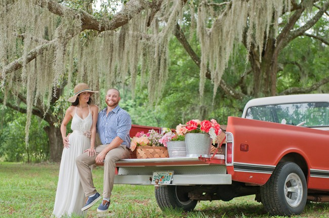 Bride and groom sitting on red vintage truck bed with buckets of flowers