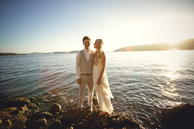 Bride and groom standing on shoreline of orcas island  captured by aubrey joy photography