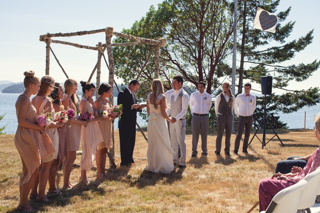 Bride and groom taking vows during wedding ceremony on orcas island  captured by aubrey joy photography