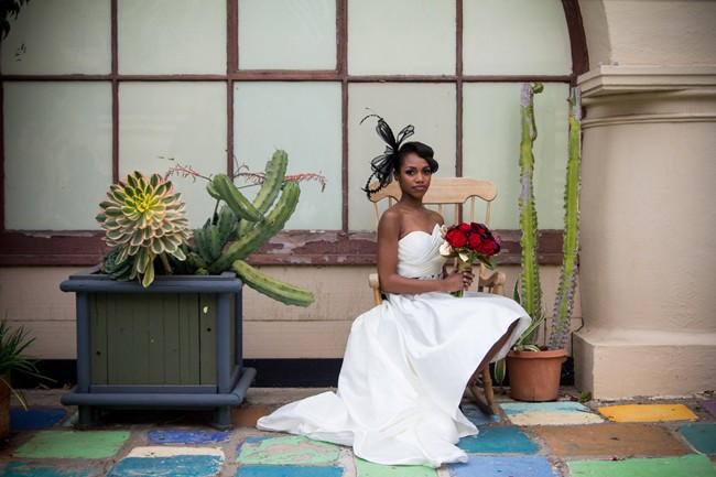 Bride sitting in chair with red roses in Balboa Park