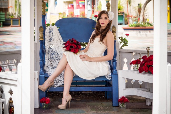 Bride sitting in gazebo in Balboa Park with red roses