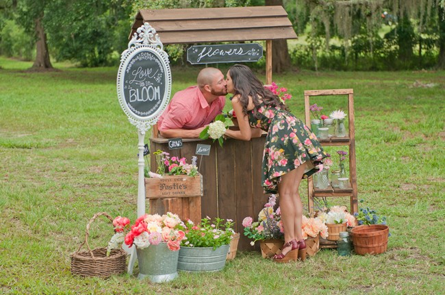 Engaged couple kissing at flower stand