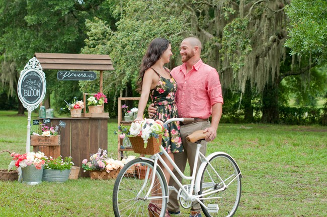Flower stand engagement shoot with couple and vintage bike