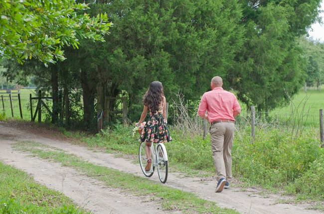 Girl on vintage bike with fiance chasing her