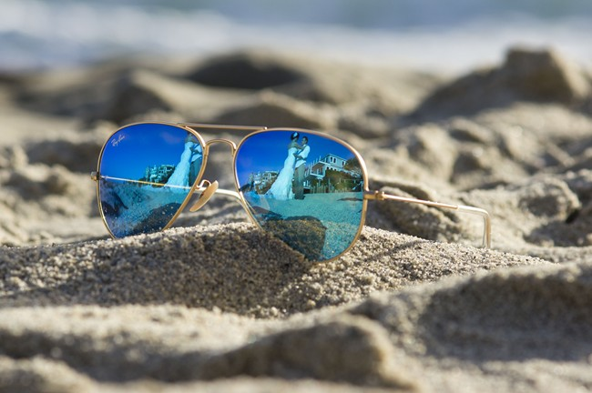 rayban sunglasses on sand with reflection of couple