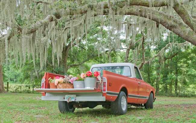 Red ford truck with flower buckets on truck bed