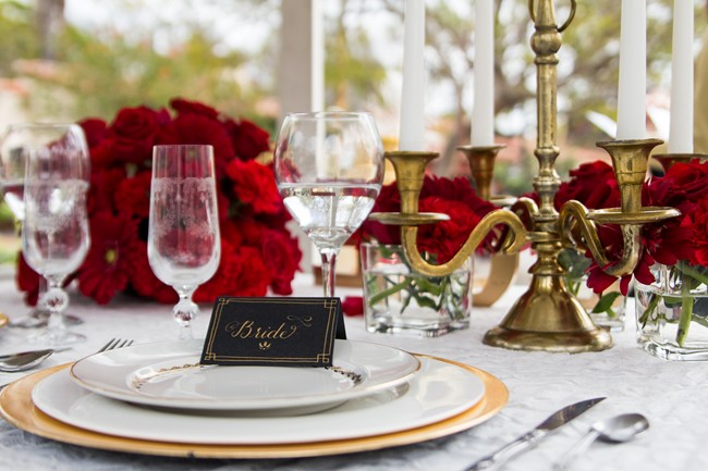 Red roses with gold accents table setting with a place card at Balboa Park
