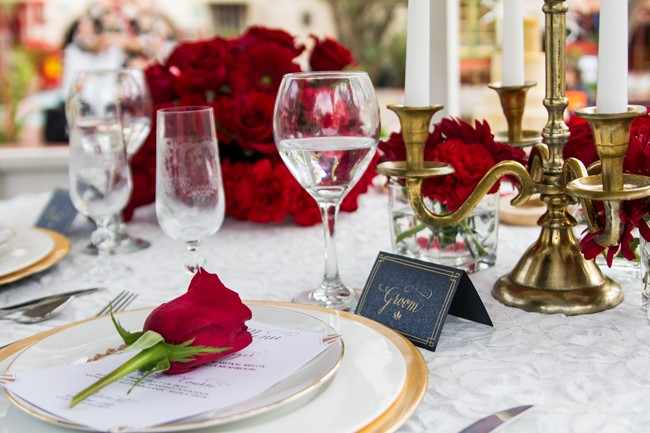 Red roses with gold accents table setting with a place card for the groom at Balboa Park
