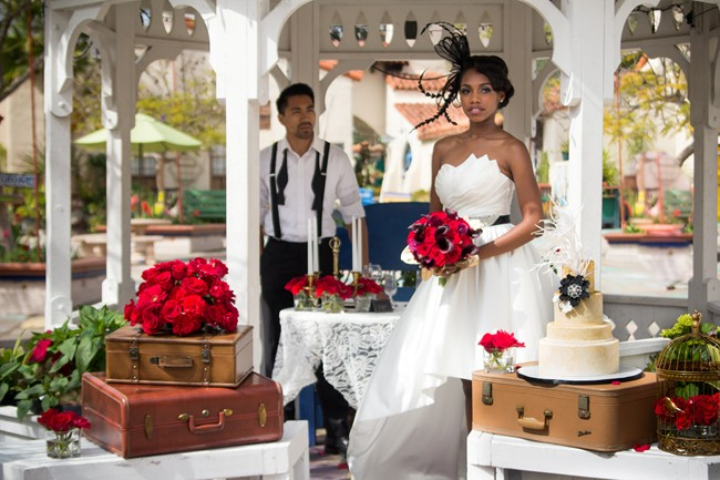 Vintage suite cases, gold wedding cake bride and groom with red roses at Balboa Park