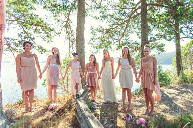 bride and bridesmaids in purple and pink dresses holding hands  captured by aubrey joy photography