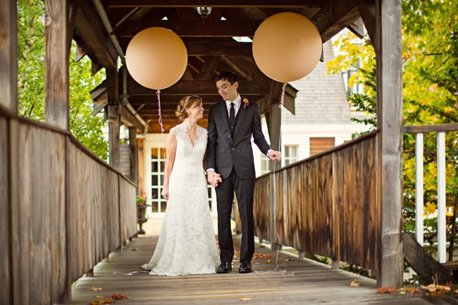 bride and groom holding peach color geronomo balloons
