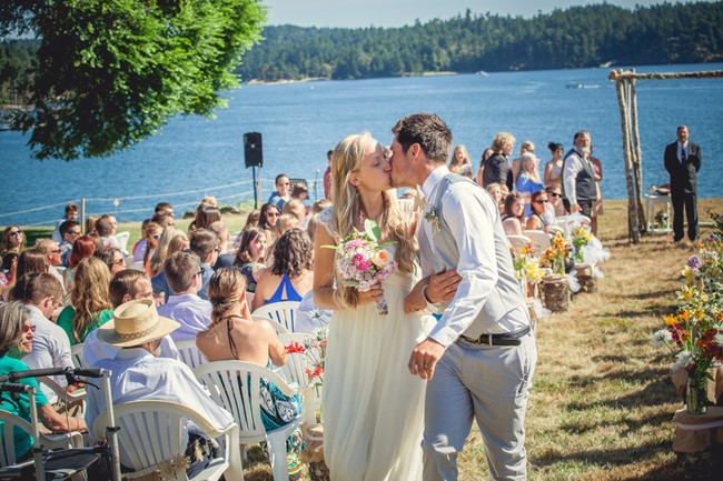 bride and groom kissing while they walk down aisle on orcas island  captured by aubrey joy photography
