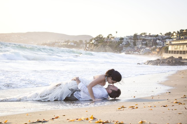 couple lay on sand at Laguna Beach