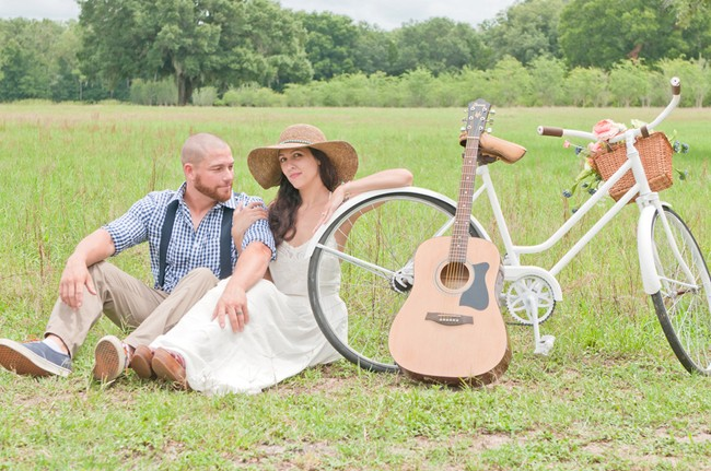 bride and groom sitting in field with vintage bike and guitar