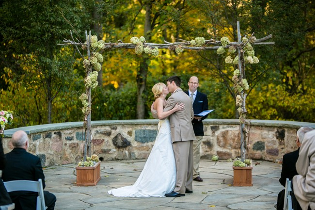 bride and groom stading at altar wood hydrageas at Sweetwater Farm Grace Winery