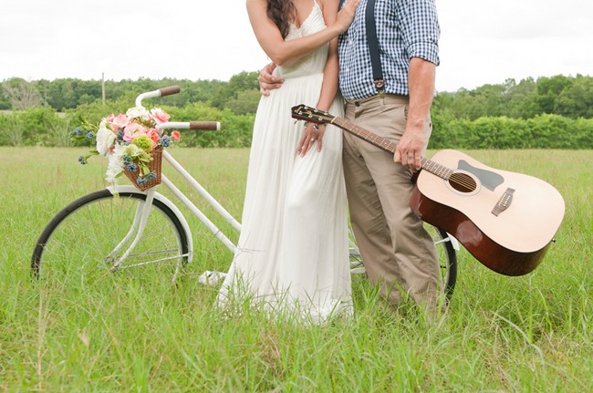 bride and groom standing togther with vintage bike and guitar