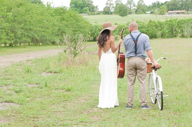 bride and groom walking in field with guitar and vintage bike