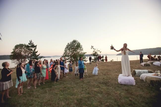 bride throwing boquet on orcas island  captured by aubrey joy photography