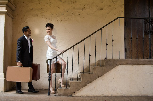 bride wearing Iselle Design Studio and groom walking up the stairs carrying vintage suitcase in balboa park