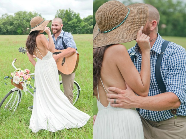 couple standing in field with vintage bike and guitar and floppy hat