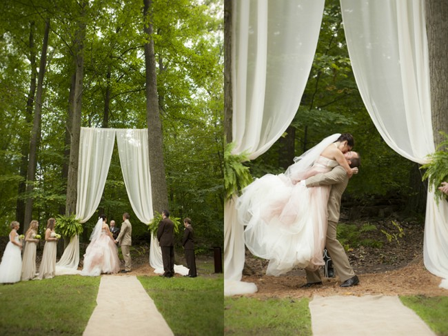 white sheer material hanging from trees for ceremony altar