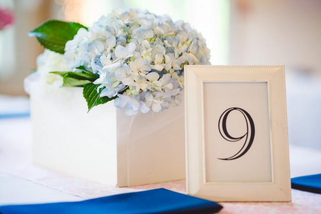 White and blue hydrangea and white frame table number at navy blue and pink wedding reception  at North Carolina Arboretum