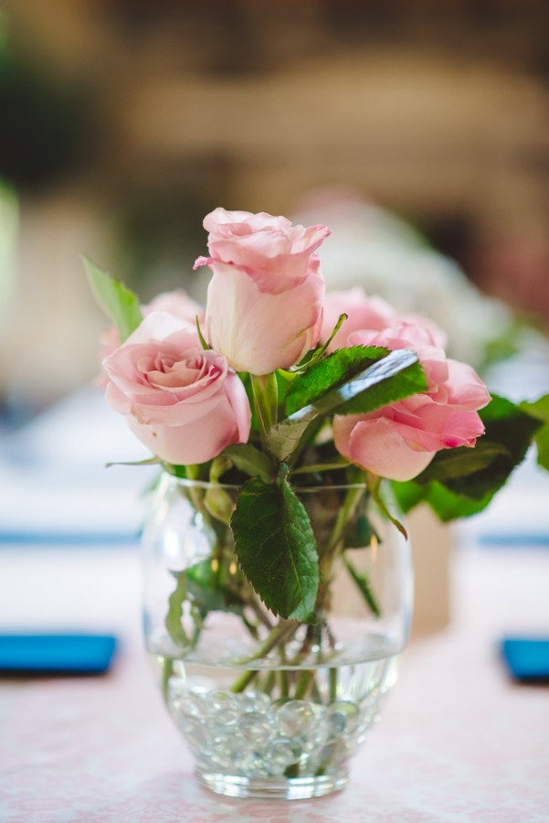 Pink roses in vase at pink and navy blue wedding reception  at North Carolina Arboretum